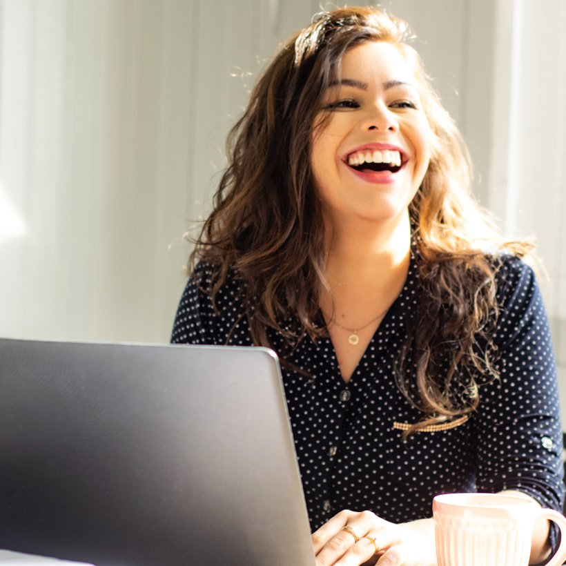 business-woman-working-on-her-laptop-and-laughing